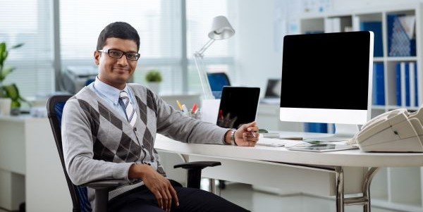 Portrait of cheerful Indian manager at his table looking at the camera